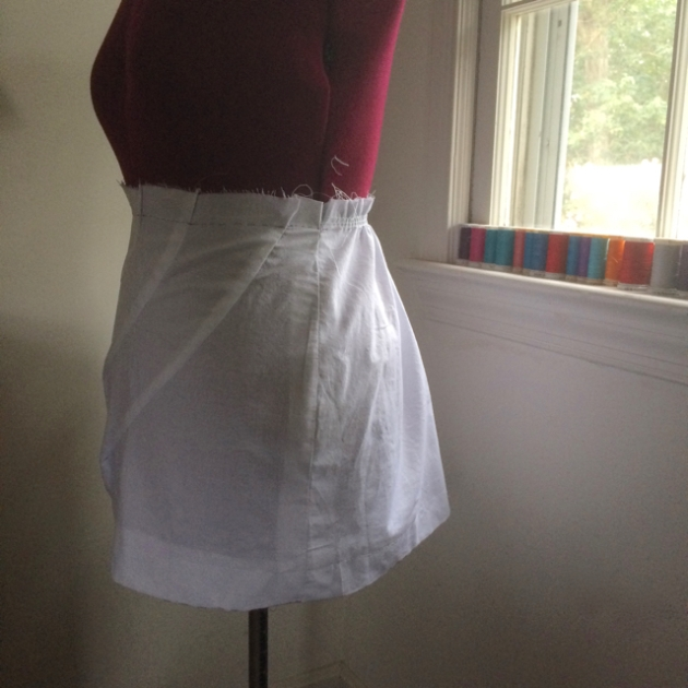 Muslin mockup of asymmetrical curved darts mini skirt